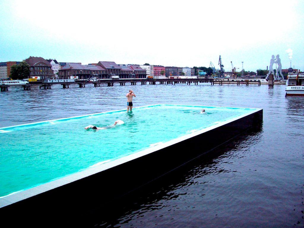"""El """"barco de baño"""" está compuesto por cuatro elementos una embarcación del tipo gabarra para bañarse, una playa, un puente como elemento conector y su container. Juntos crean un baño móvil a lo largo del río Spree que, en invierno, puede ser utilizado como pista de patinaje sobre hielo."""