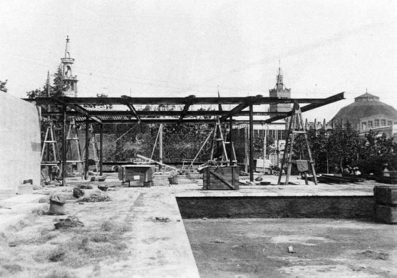 Foto del Pabellón de Barcelona con parte de la estructura de cubierta terminada, y apoyada en 6 pilares y numerosos caballetes auxiliares apeando los voladizos.