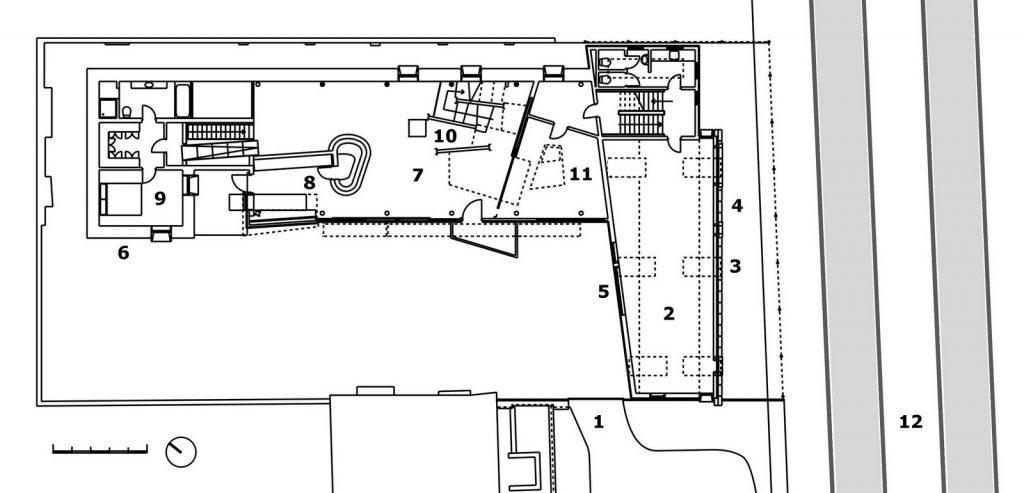 Primera planta de la Casa de Paja (2001): 1. Callejón 2. Estudio 3. Proyección de gavión 4. Fachada de sacos 5. Fachada acolchada 6. Muro de paja 7. Estar 8. Cocina con fresquera 9. Dormitorio 10. Biblioteca-torre 11. Comedor 12. Ferrocarril