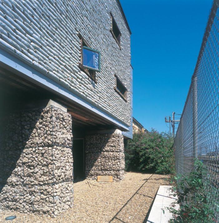 La fachada a la vía del tren está construida con gaviones hormigón reciclado, sacos de arena, y reutilizando viejas traviesas en marcos de ventanas Fotografías Paul Smoothy