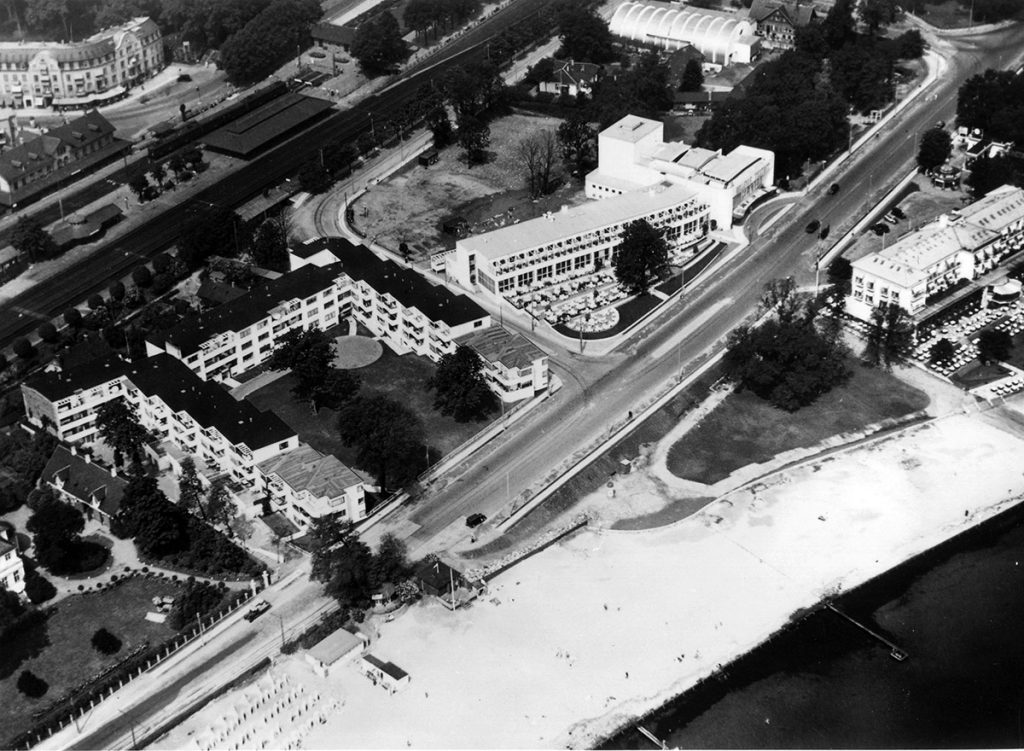 Conjunto de edificios terminados en la playa Bellevue en 1937. De izquierda a derecha apartamentos 'Bellavista' (1931-34), Restaurante y Teatro 'Bellevue'(1935-37) y escuela de hípica 'Mattsson' (1933-34). El club de piragüismo se contruiría al año siguiente justo frente al bloque residencial. El antiguo Hotel de la Playa aún permanecía flanqueando el acceso al recinto de la playa (derecha).