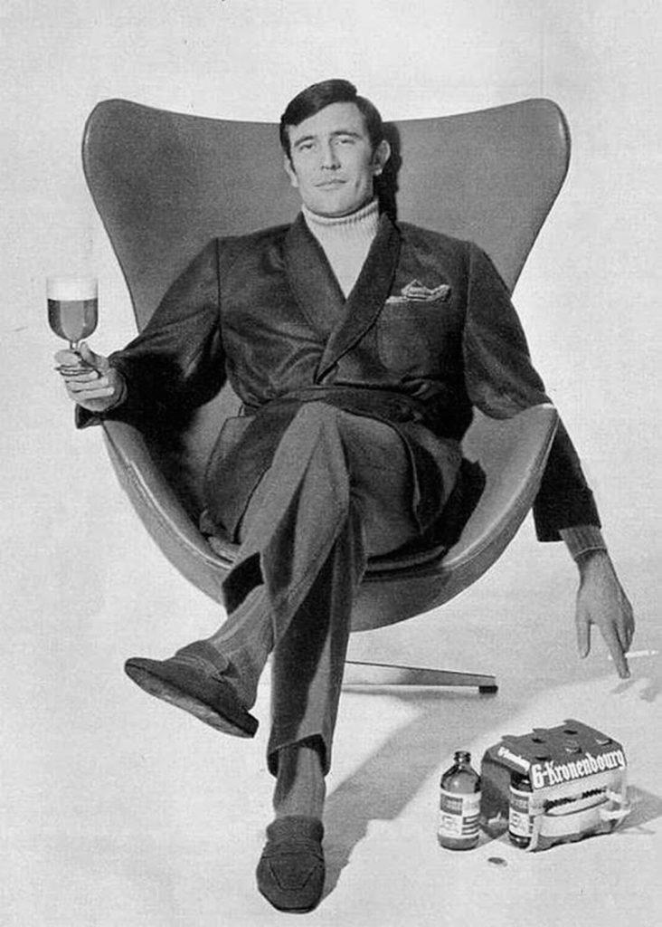 George Lazenby sentado en la silla del huevo de Arne Jacobsen con una Kronenbourg
