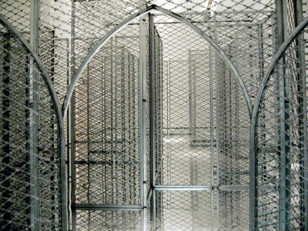 Akropolis Now, Kendell Geers, 2004. Visto aquí. La obra consiste en 18 paneles verticales de malla de alambre con concertinas en posición vertical y en el interior de una estructura modular metálica. | Fuente: http://lamiradapaseante.blogspot.com/2013/11/akropolis-now-concertinas.html